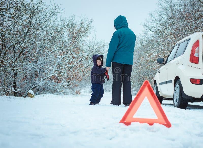 Femme avec un enfant sur la route d'hiver photo stock