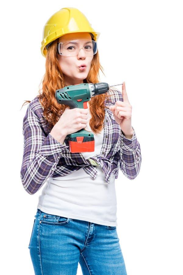 femme avec un foret dans des vêtements protecteurs faisant la réparation à la maison image stock