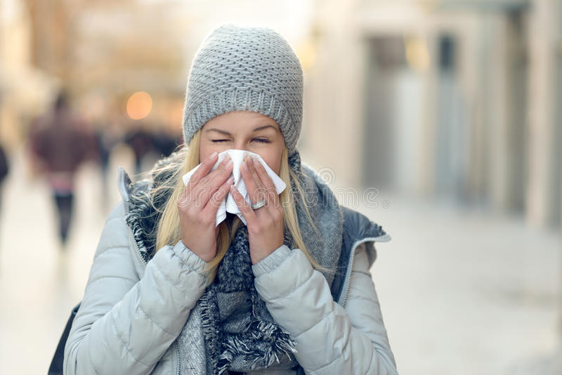 Femme avec un froid saisonnier d'hiver soufflant son nez photo stock