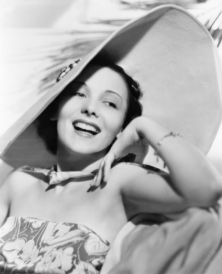 Femme avec un grand chapeau riant et profitant d'un agréable moment (toutes les personnes représentées ne sont pas plus long viva photo libre de droits