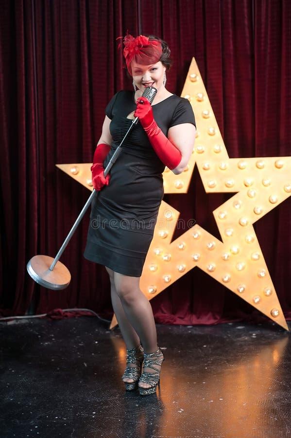 Femme avec un microphone sur la scène de bruit photos libres de droits