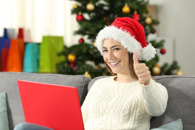 Femme avec un ordinateur portable et des pouces sur Noël photos libres de droits