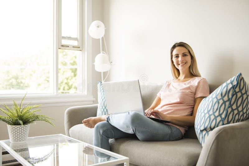 Femme avec un ordinateur portable sur le sofa à la maison photos libres de droits