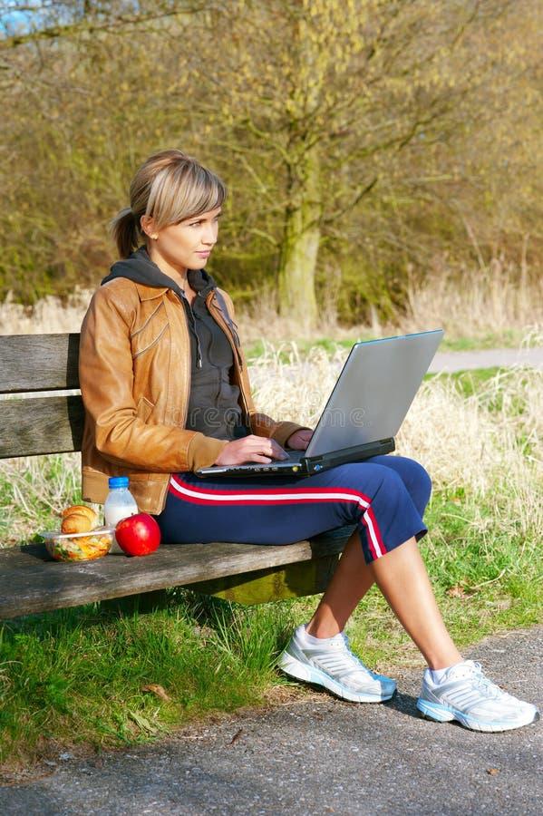 Femme avec un ordinateur portatif à l'extérieur photo libre de droits
