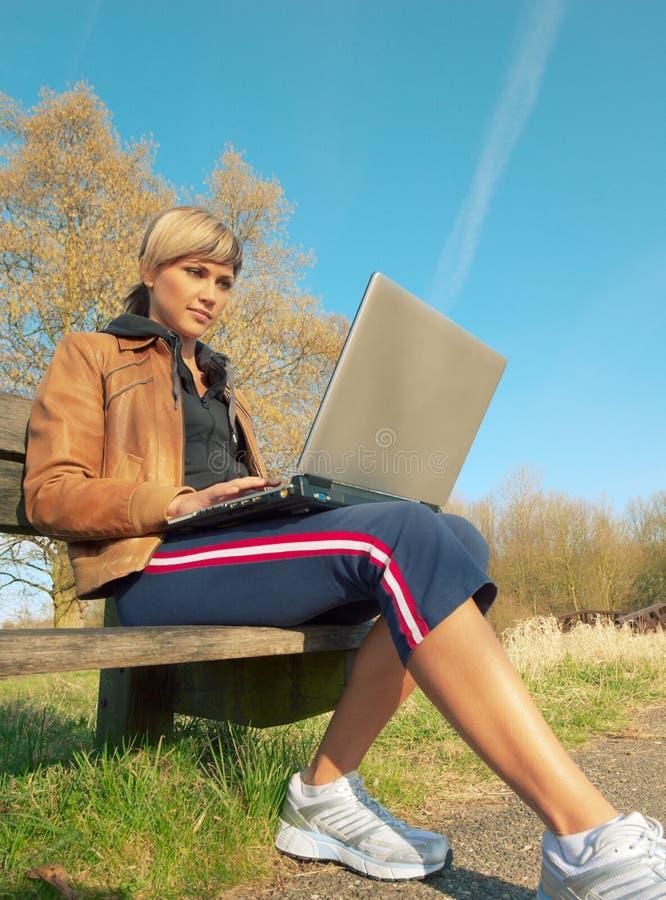 Femme avec un ordinateur portatif à l'extérieur photo stock