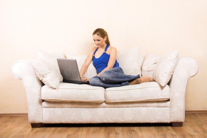 Femme avec un ordinateur portatif sur un salon photos libres de droits