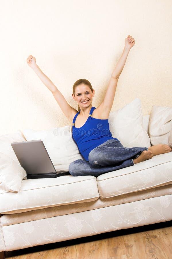 Femme avec un ordinateur portatif sur un salon photos stock