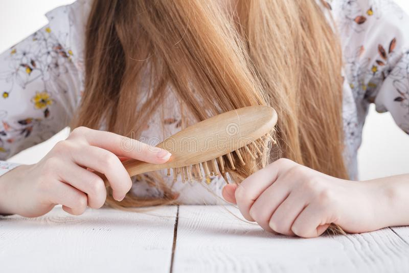 Femme avec un peigne dans ses cheveux de problème de mains photographie stock