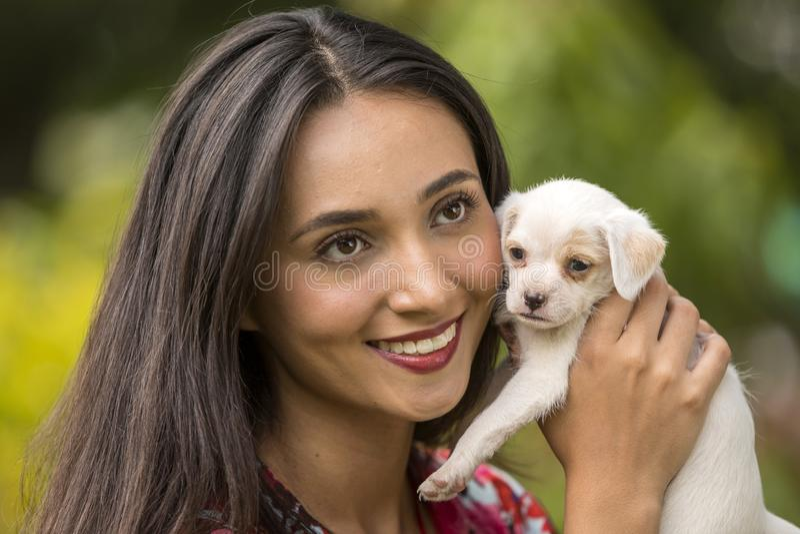 Femme avec un petit chiot blanc dans des ses mains photos libres de droits