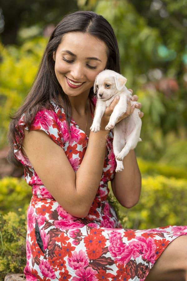 Femme avec un petit chiot blanc dans des ses mains image stock