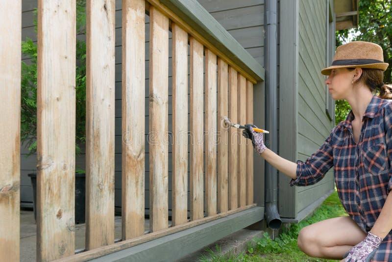 Femme avec un pinceau peignant les balustrades en bois de terrasse Tir ext?rieur photos stock