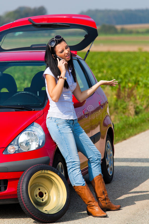 Femme avec un pneu dans une panne de véhicule photo libre de droits
