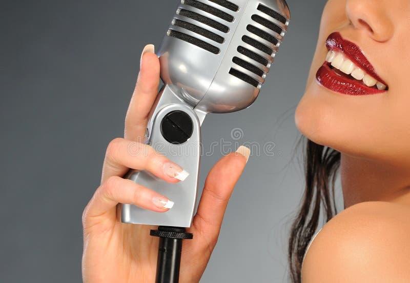Femme avec un rétro microphone photographie stock libre de droits