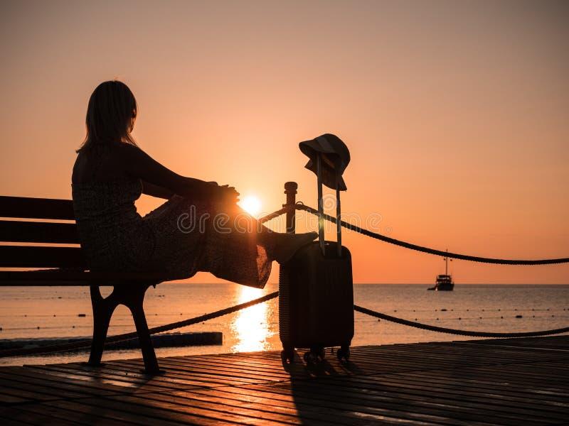 Femme avec un sac de voyage se reposant sur la jetée par la mer Un petit bateau est évident dans la distance photographie stock