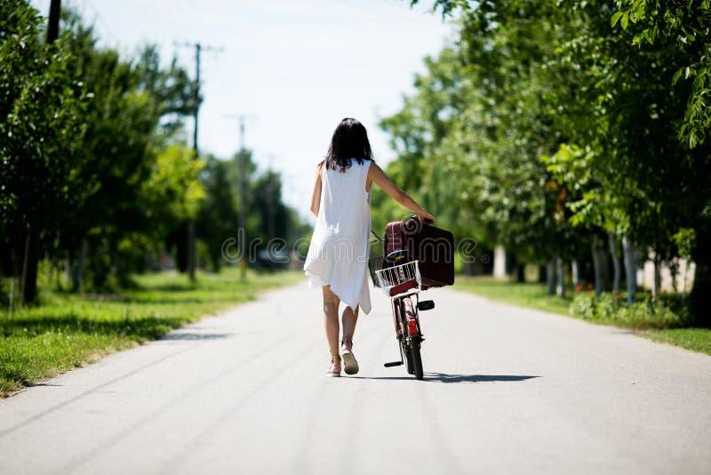 Femme avec un vélo de vintage dans une campagne image libre de droits