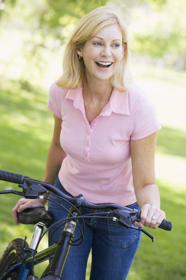 Femme avec un vélo souriant à l'extérieur image stock