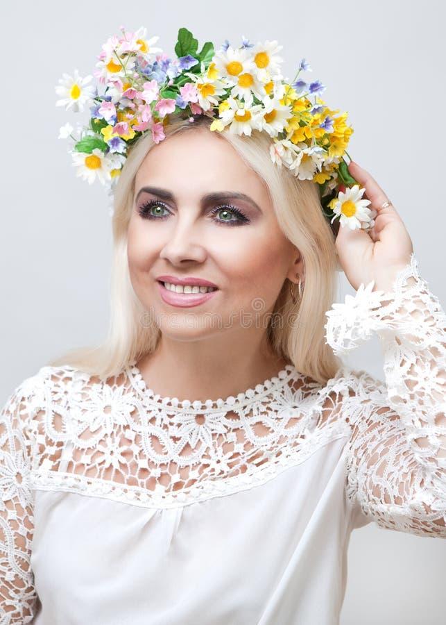 Femme avec une guirlande sur la tête des fleurs artificielles photos stock