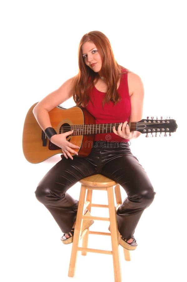 Femme avec une guitare acoustique photographie stock libre de droits