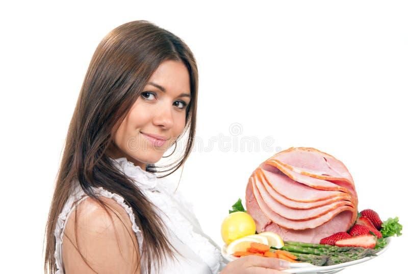Femme avec une plaque avec du jambon coupé en tranches photo stock