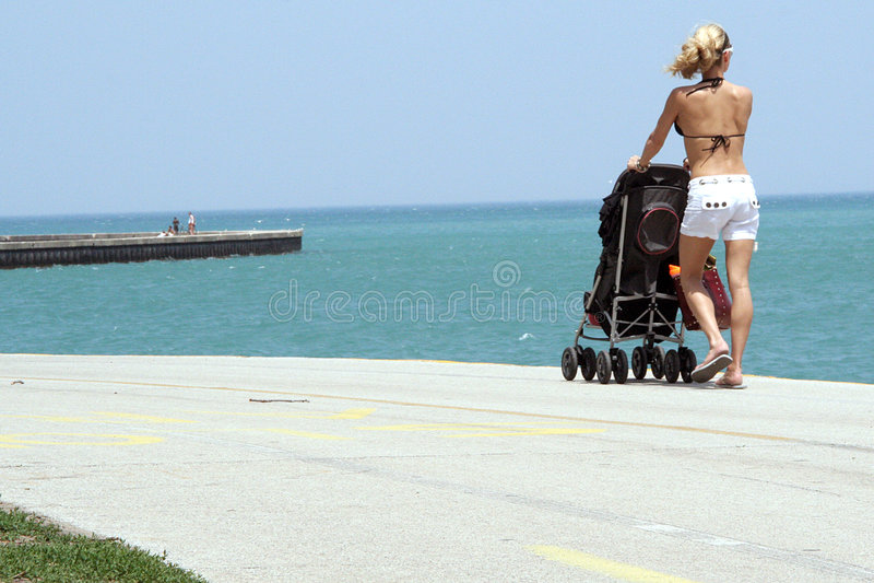 Femme avec une poussette sur la plage images stock