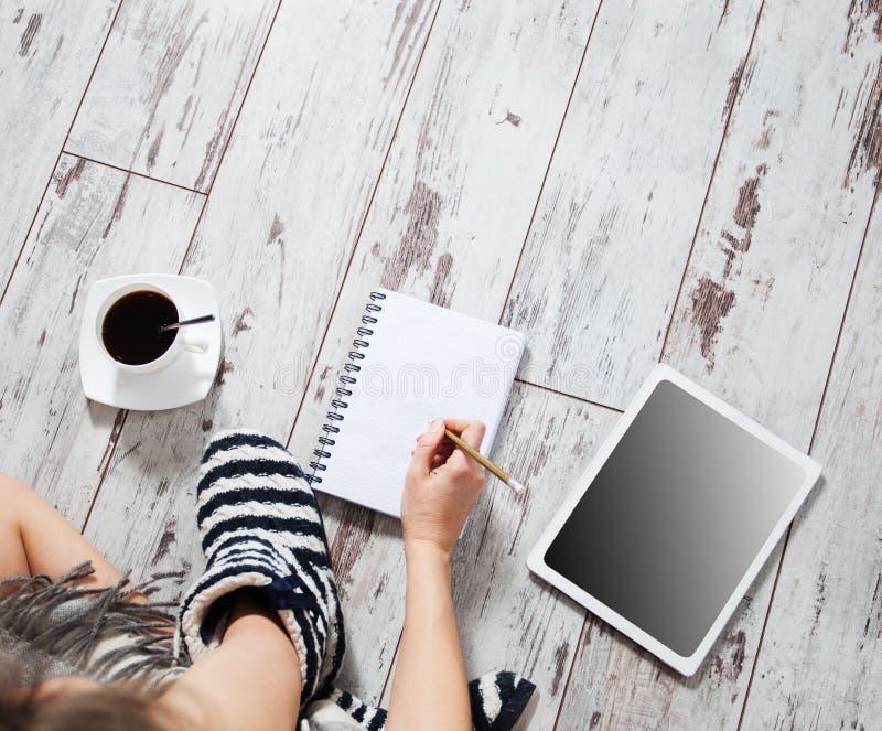 Femme avec une tasse de café, de bloc-notes et de comprimé images stock