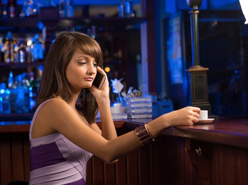 Femme avec une tasse de café et de téléphone portable photographie stock