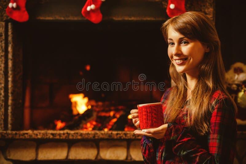 Femme avec une tasse par la cheminée Jeune femme attirante images libres de droits