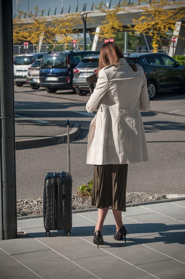 Femme avec une valise attendant un taxi à l'aéroport photos libres de droits