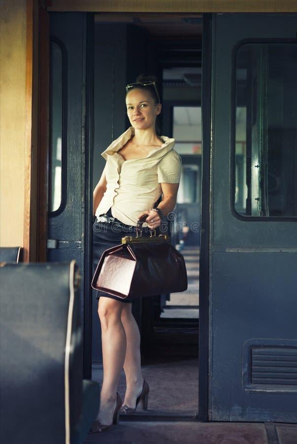 Femme avec une valise dans le rétro train image stock