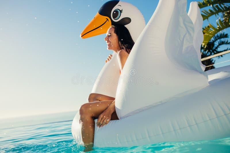 Femme ayant l'amusement sur le jouet de flottement dans la piscine images stock