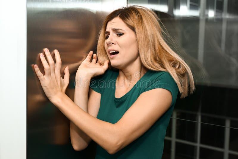 Femme ayant l'attaque de panique dans l'ascenseur image libre de droits