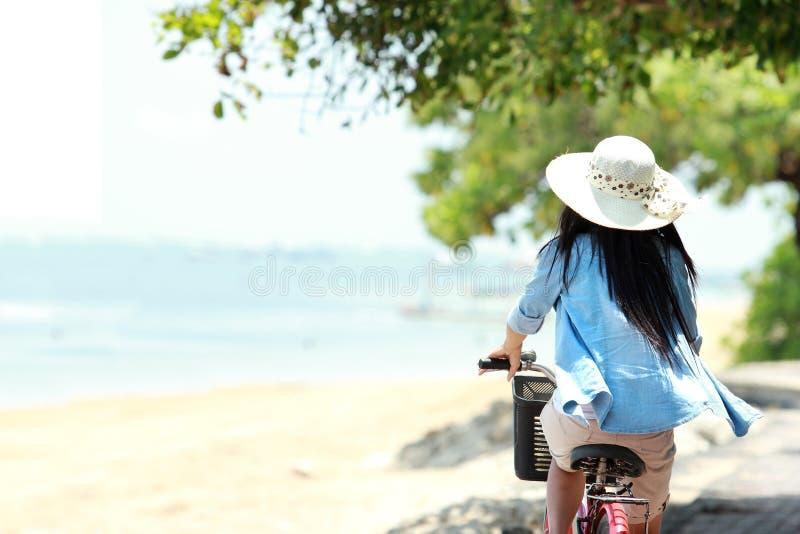 Femme ayant la bicyclette d'équitation d'amusement à la plage photos stock