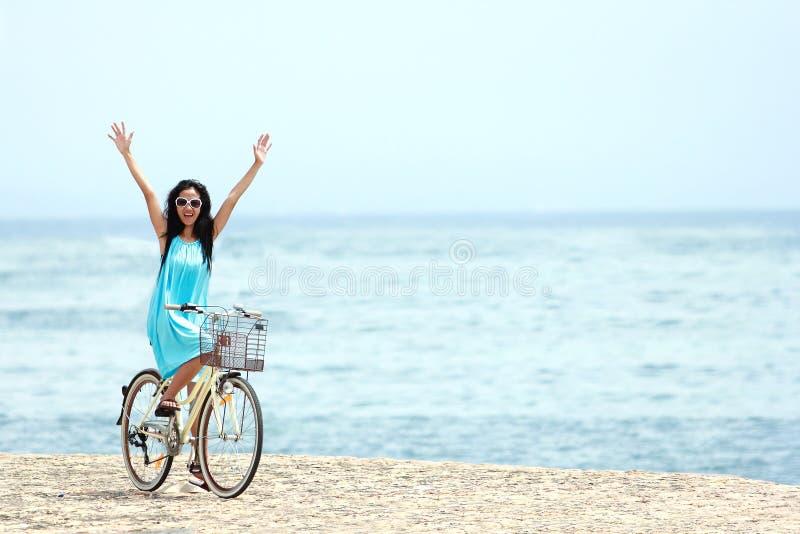 Femme ayant la bicyclette d'équitation d'amusement à la plage photo stock