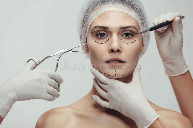 Femme ayant la chirurgie cosmétique de visage image libre de droits