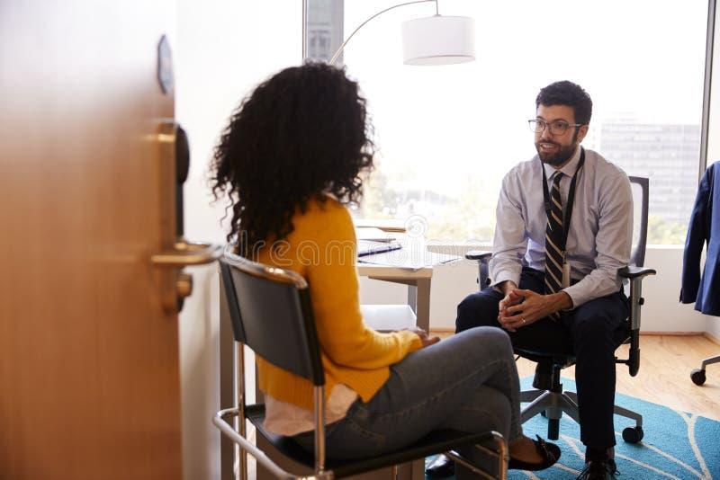 Femme ayant la consultation avec docteur masculin Viewed Through Door de bureau d'hôpital images libres de droits
