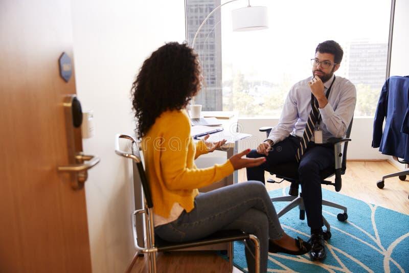 Femme ayant la consultation avec docteur masculin Viewed Through Door de bureau d'h?pital photos libres de droits