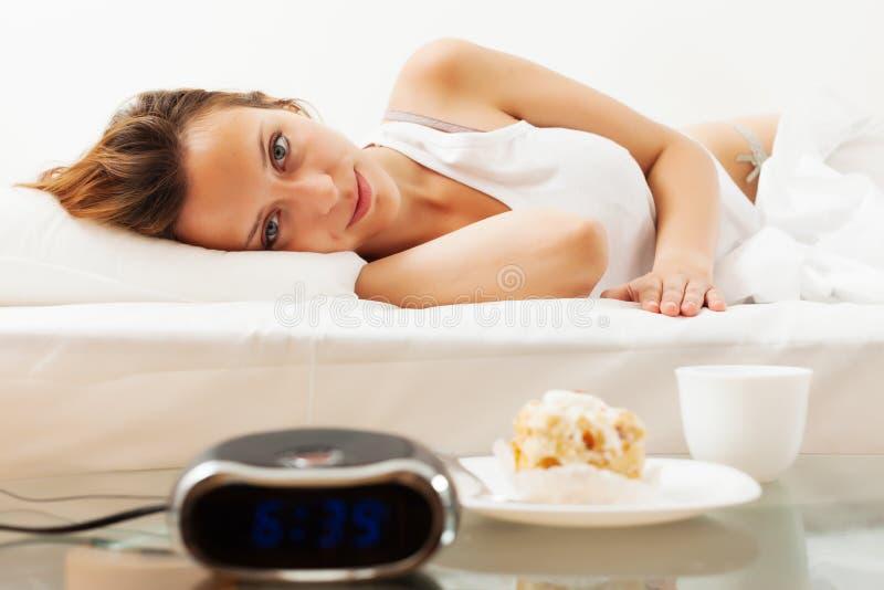 Femme ayant le gâteau et le café doux dans le matin images stock