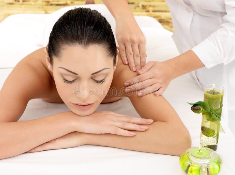 Femme ayant le massage de l'épaule dans le salon de station thermale image libre de droits