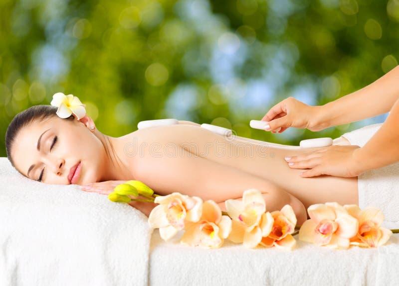 Femme ayant le massage en pierre chaud dans le salon de station thermale. images libres de droits