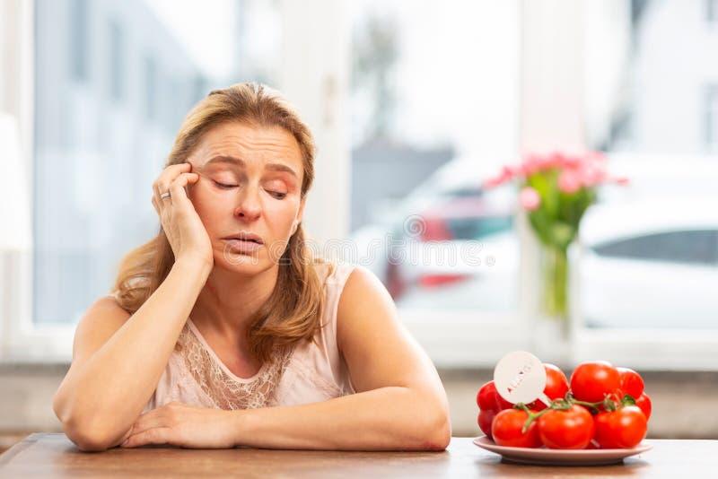 Femme ayant le souhait pour manger des tomates mais souffrant de l'allergie photographie stock