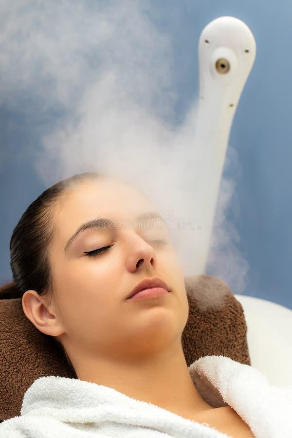 Femme ayant le traitement à la vapeur facial dans la station thermale image libre de droits