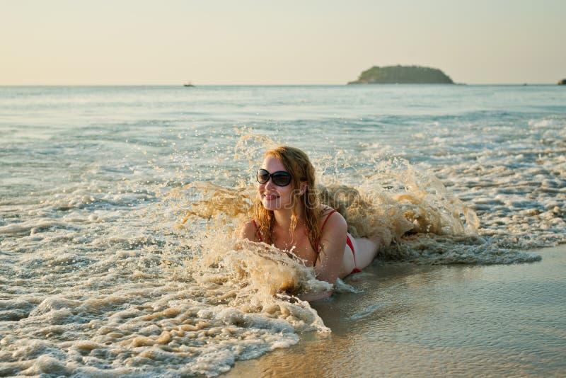Femme ayant un amusement tout en nageant en mer image stock