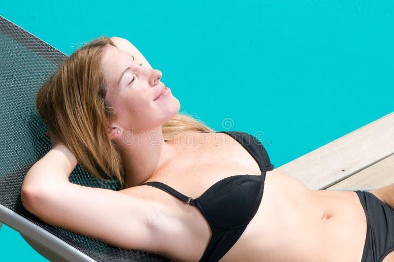 Femme ayant un bain du soleil près d'une piscine photos stock