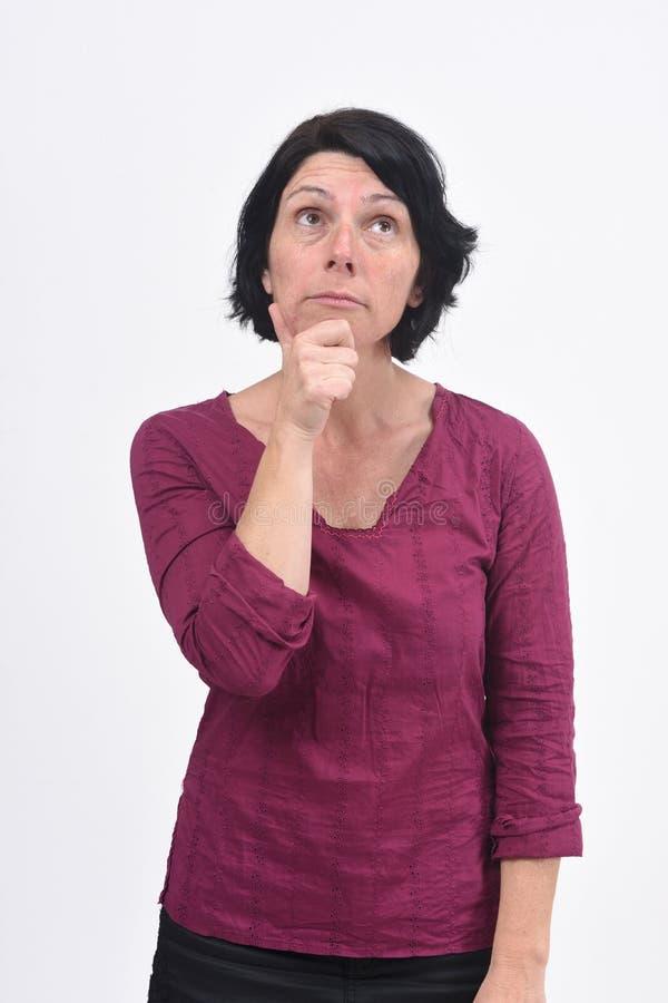 Femme ayant un doute ou une question sur le fond blanc photographie stock