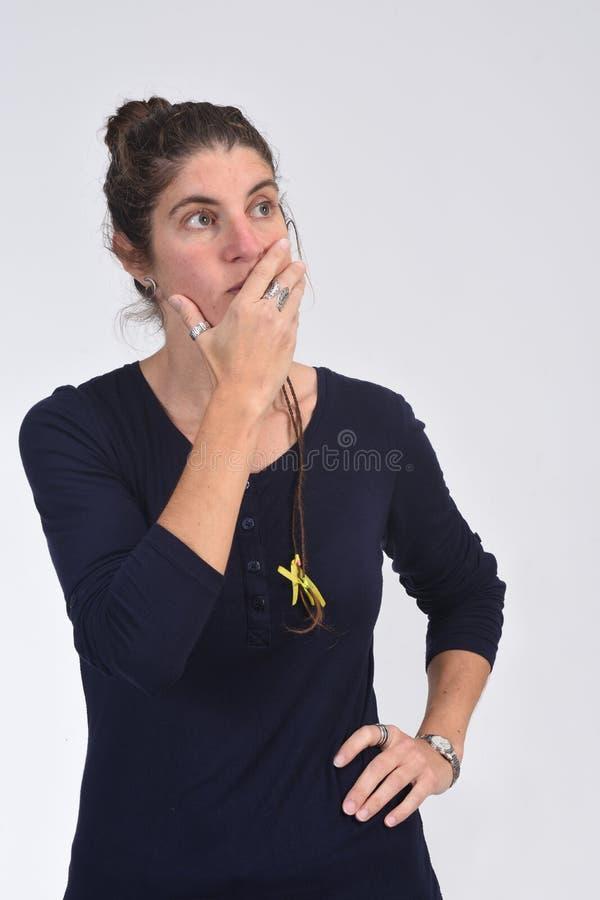 Femme ayant un doute ou une question sur le fond blanc images stock