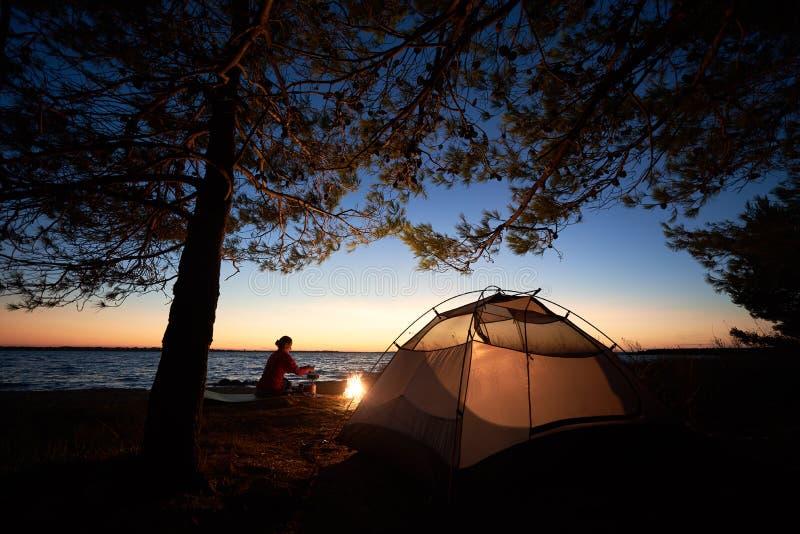 Femme ayant un repos la nuit campant près de la tente de touristes, feu de camp sur le bord de mer sous le ciel étoilé photo stock