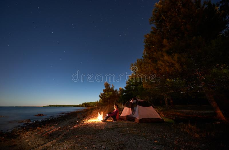 Femme ayant un repos la nuit campant pr?s de la tente de touristes, feu de camp sur le bord de mer sous le ciel ?toil? photographie stock