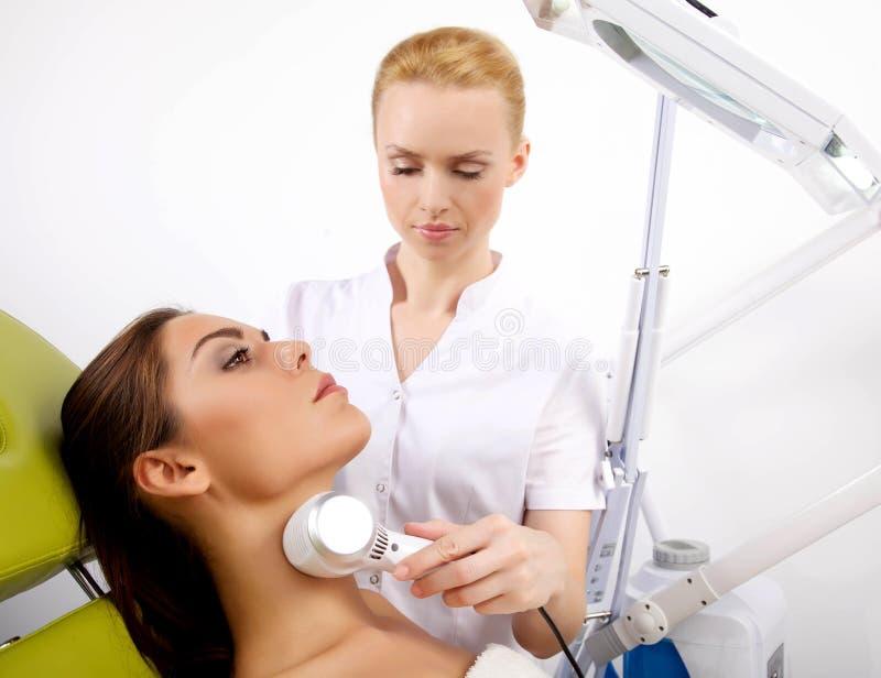 Femme ayant un traitement facial stimulant d'un thérapeute photos stock