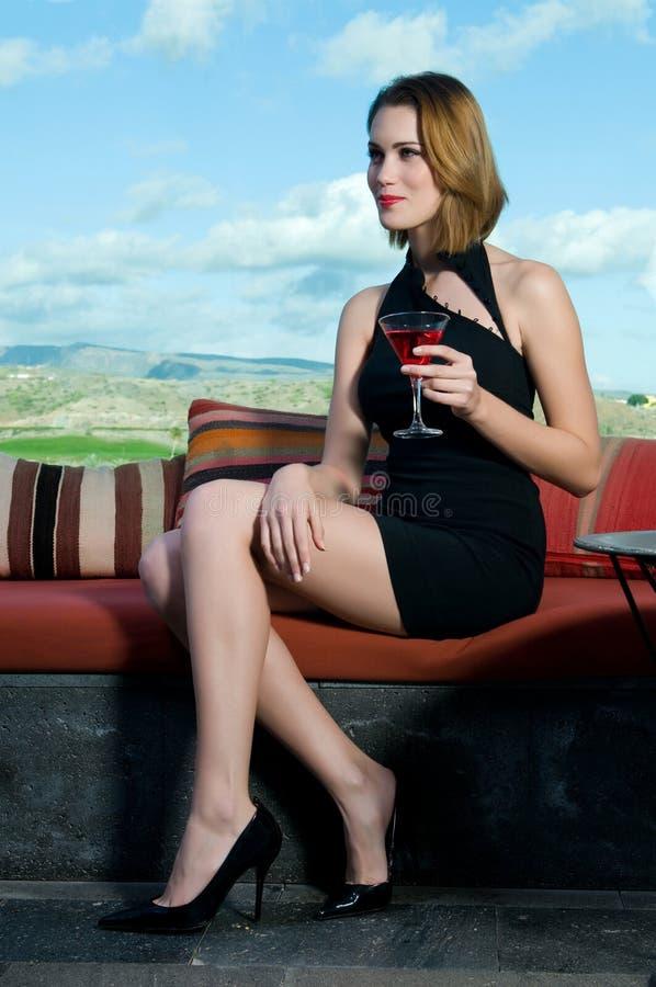 Femme ayant une boisson alcoolisée martini photos stock