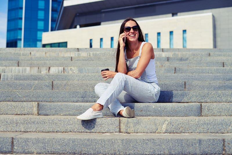 Femme ayant une coupure sur l'air frais avec du café et causant sur t image stock